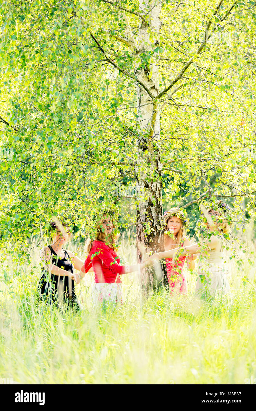 slavic girls standing under the birch-tree and holding each other hands - Stock Image