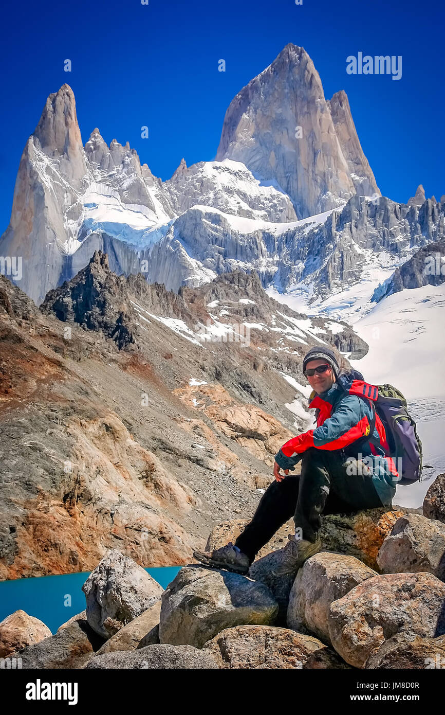 Male trekker resting on the rock in front of the stunning and impressive Mount Fitz Roy near El Chalten in Patagonia, Argentina - Stock Image