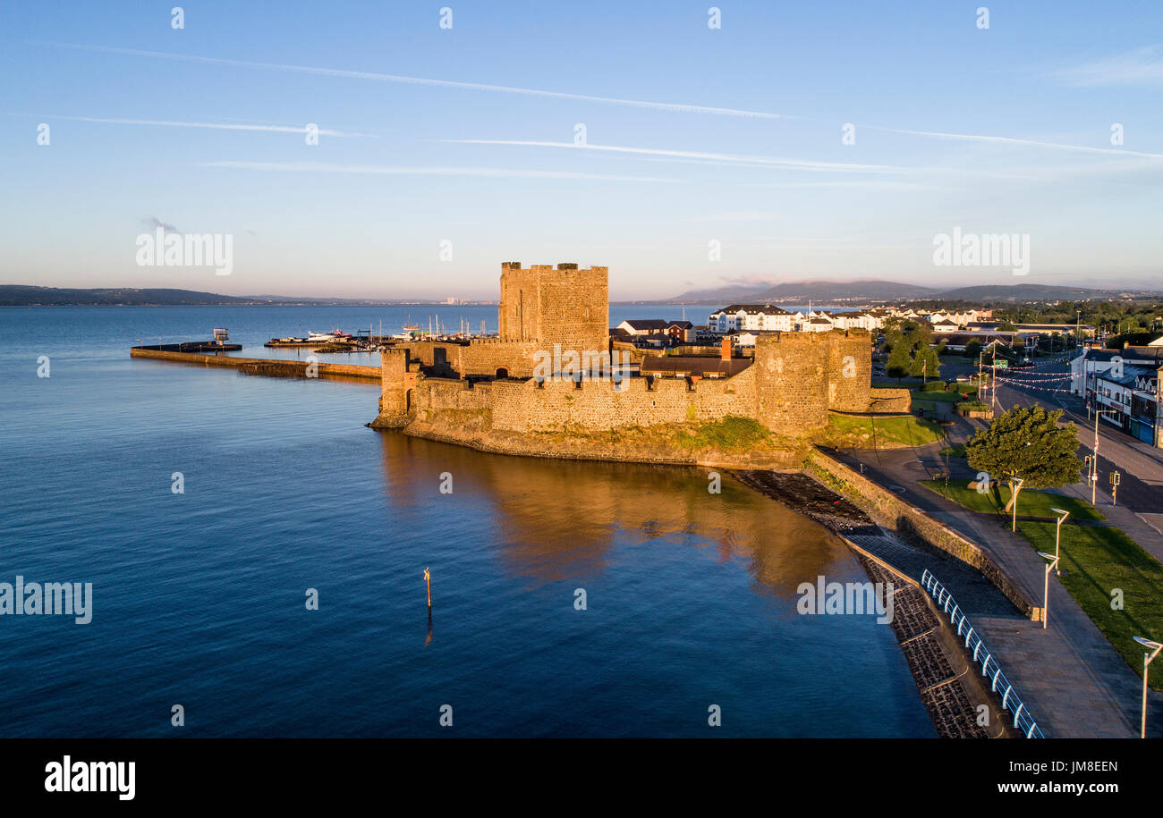 Medieval Norman Castle in Carrickfergus near Belfast, Northern Ireland. Aerial view at sunrise with far view of Belfast in the background. - Stock Image