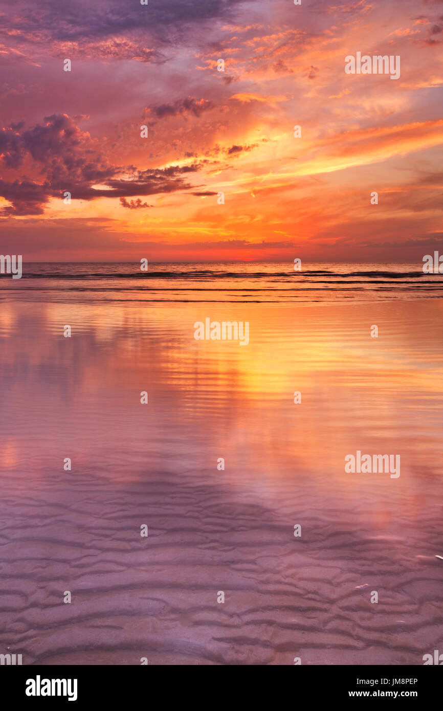 Spectacular sunset colours over sea reflected in the water