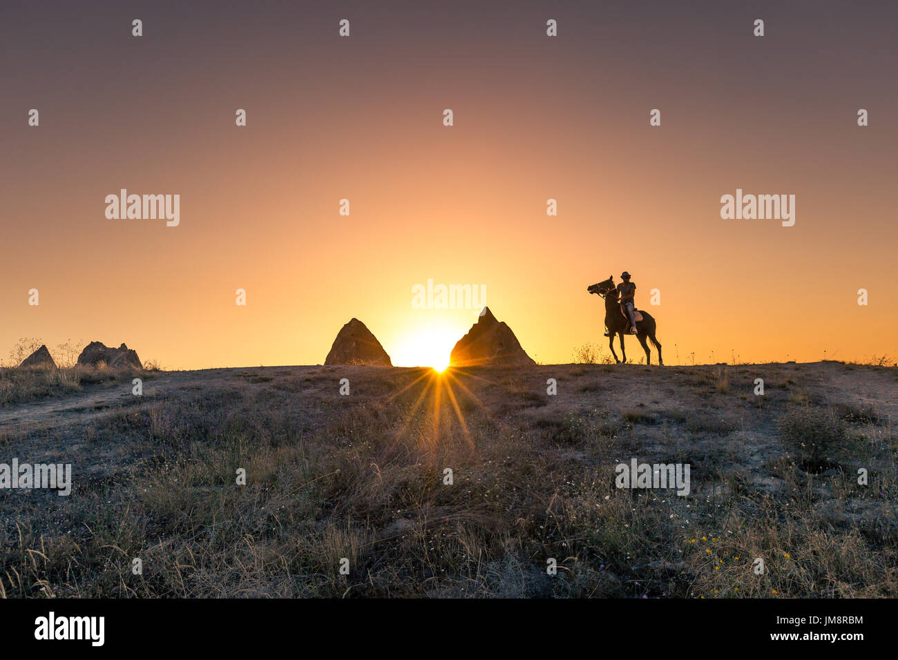 Man and horse silhouette on the background of valley at Cappadocia,Anatolia,Turkey.The great tourist attraction of Cappadocia best places to fly with  - Stock Image