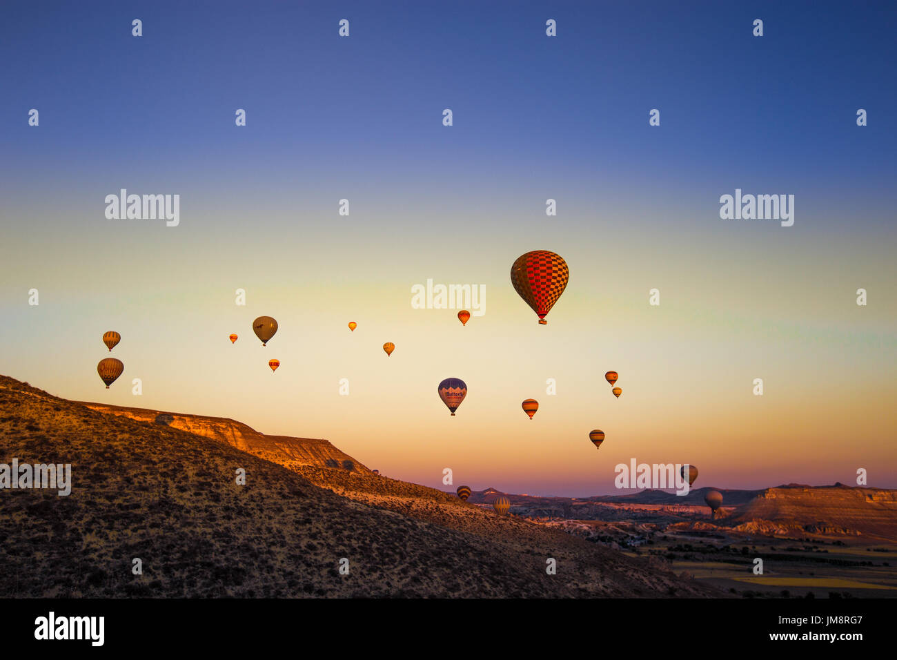Colorful hot air balloons flying over the valley at Cappadocia,Anatolia,Turkey.The great tourist attraction of Cappadocia best places to fly with hot  - Stock Image