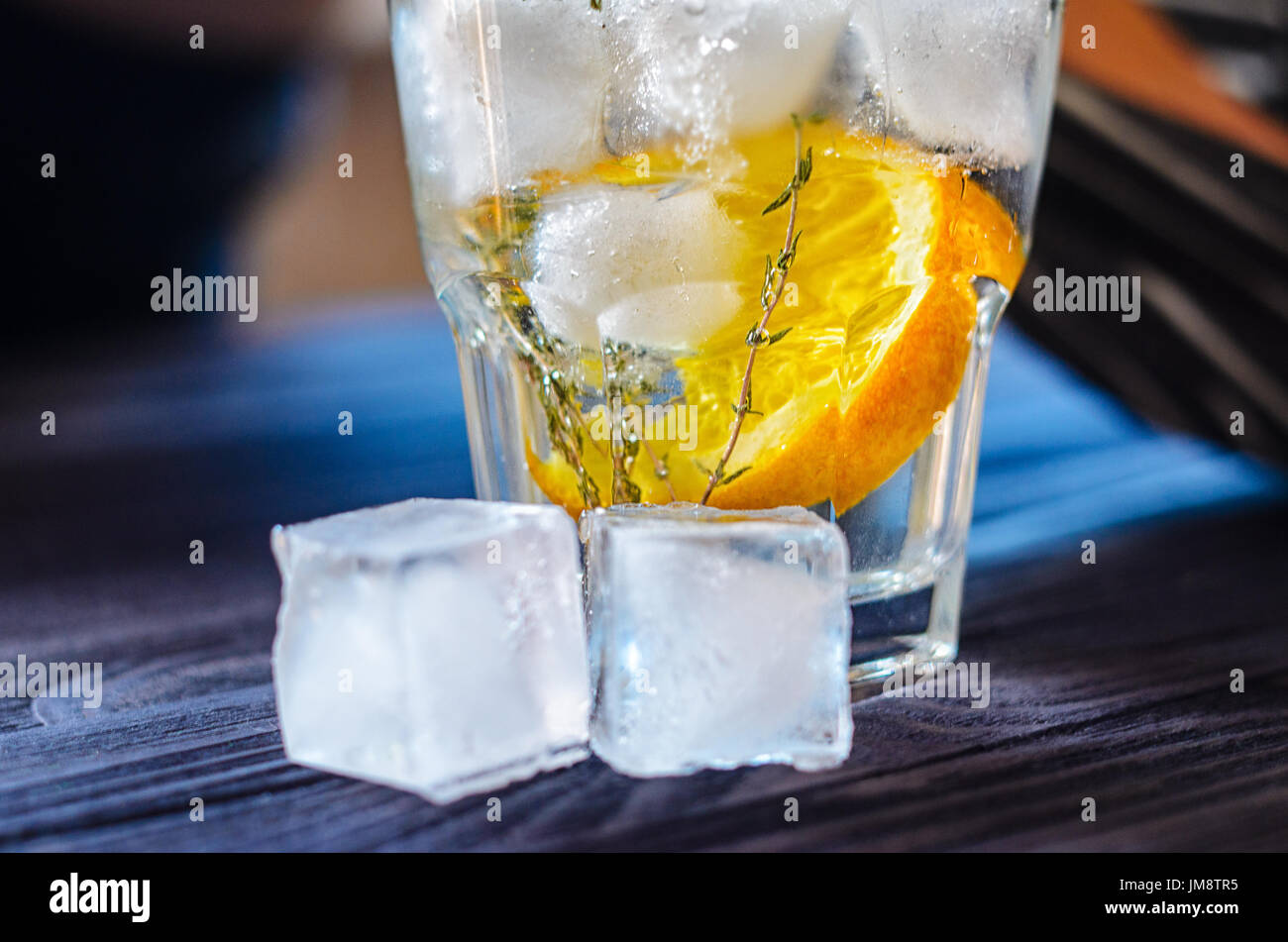 Alcoholic drink with lemon and ice in a glass on a old dark wooden table. Close up view of cold drink Stock Photo