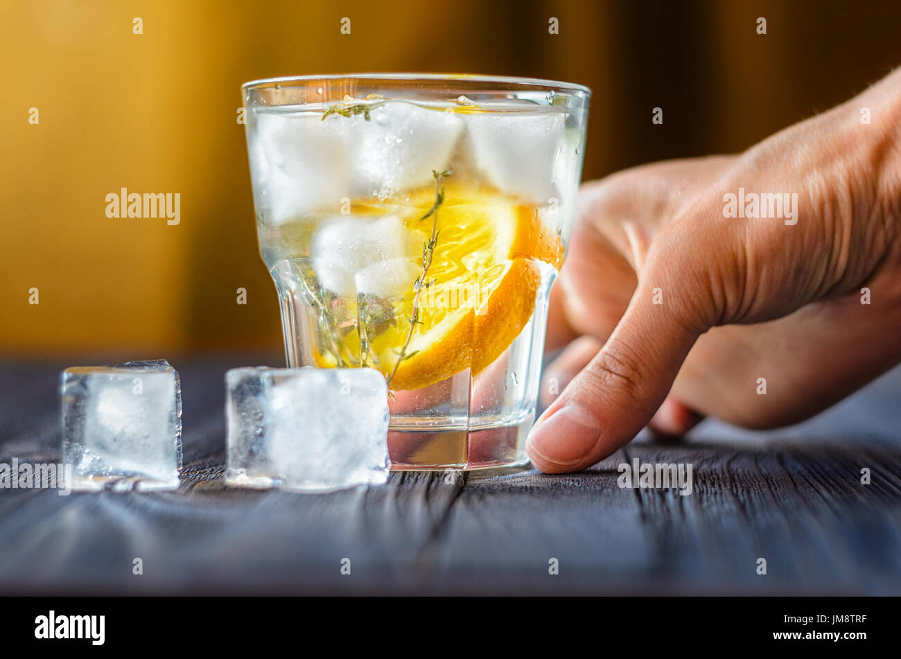 Alcoholic drink with lemon and ice in a glass on a old dark wooden table. Close up view of cold drink with human Stock Photo