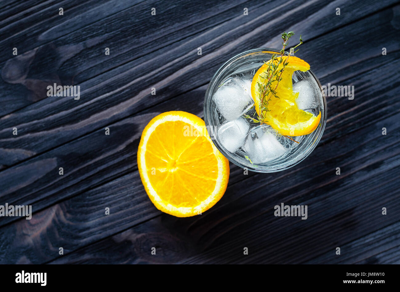 Cut lemon near the alcoholic cocktail on dark wood table top view. Blank space for text placement - Stock Image