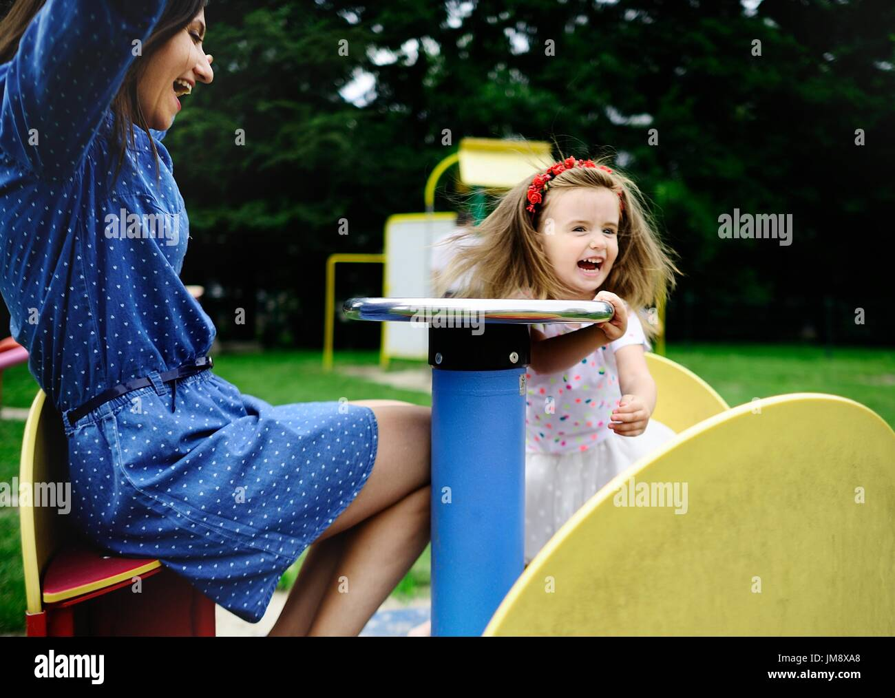 Young mother plays in the playground with the little daughter. Woman and charming girlie turning on the carousel. Serene summer day. Good mood. - Stock Image