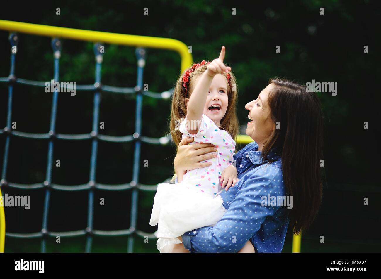Young mother plays in the playground with the little daughter. The woman holds the baby on hands. Both joyfully laugh. - Stock Image