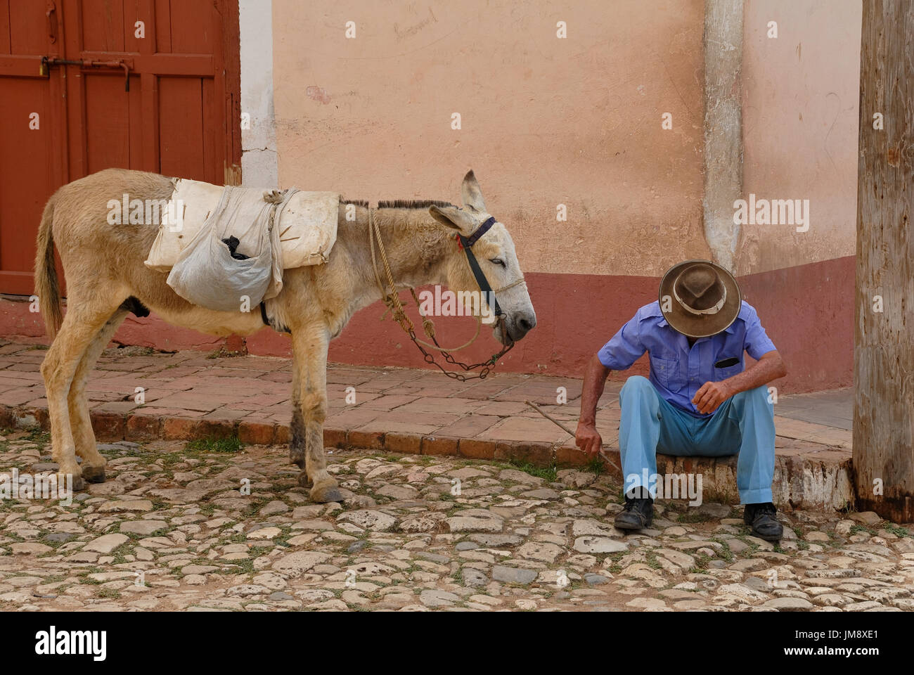 A man sitting and resting on the pavement in one of the streets in the old, colonial, part of Trinidad in Cuba. His donkey is patiently waiting. - Stock Image