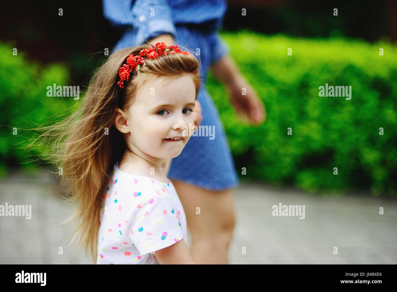 Portrait of the little girl who walks with mother. The charming baby with a wreath from red colors on the head. - Stock Image