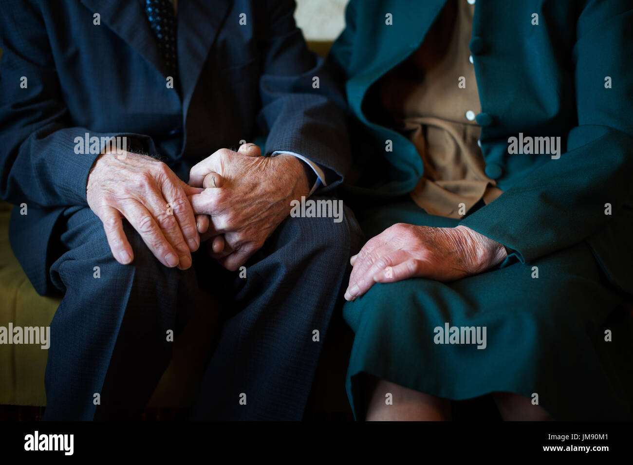 Cute 80 plus year old married couple posing for a portrait in their house. Love forever concept. - Stock Image