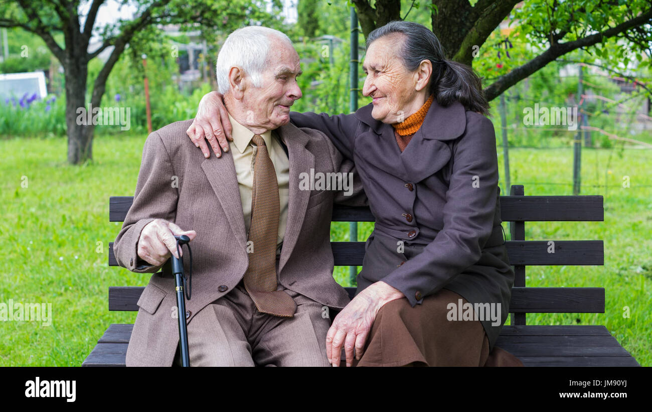 Cute 80 plus year old married couple posing for a portrait in their garden. Love forever concept. - Stock Image