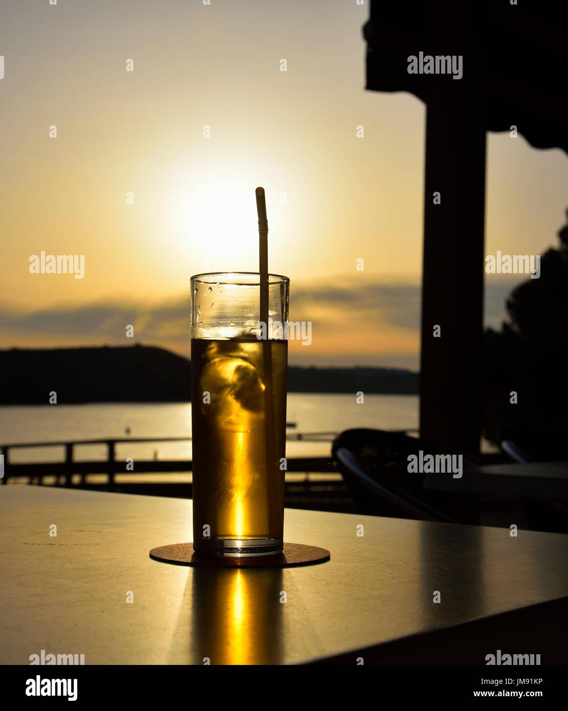 glass of gin and tonic at sunset - Stock Image