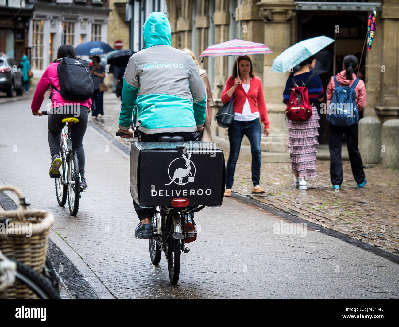 eb6378f527a Deliveroo courier - a Deliveroo food delivery courier rides in the rain in  central Cambridge UK