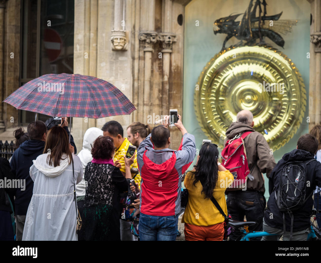 Cambridge Tourists take photos in front of the Corpus Clock at Corpus Christi College, Cambridge. It was unveilled in 2008 - Stock Image