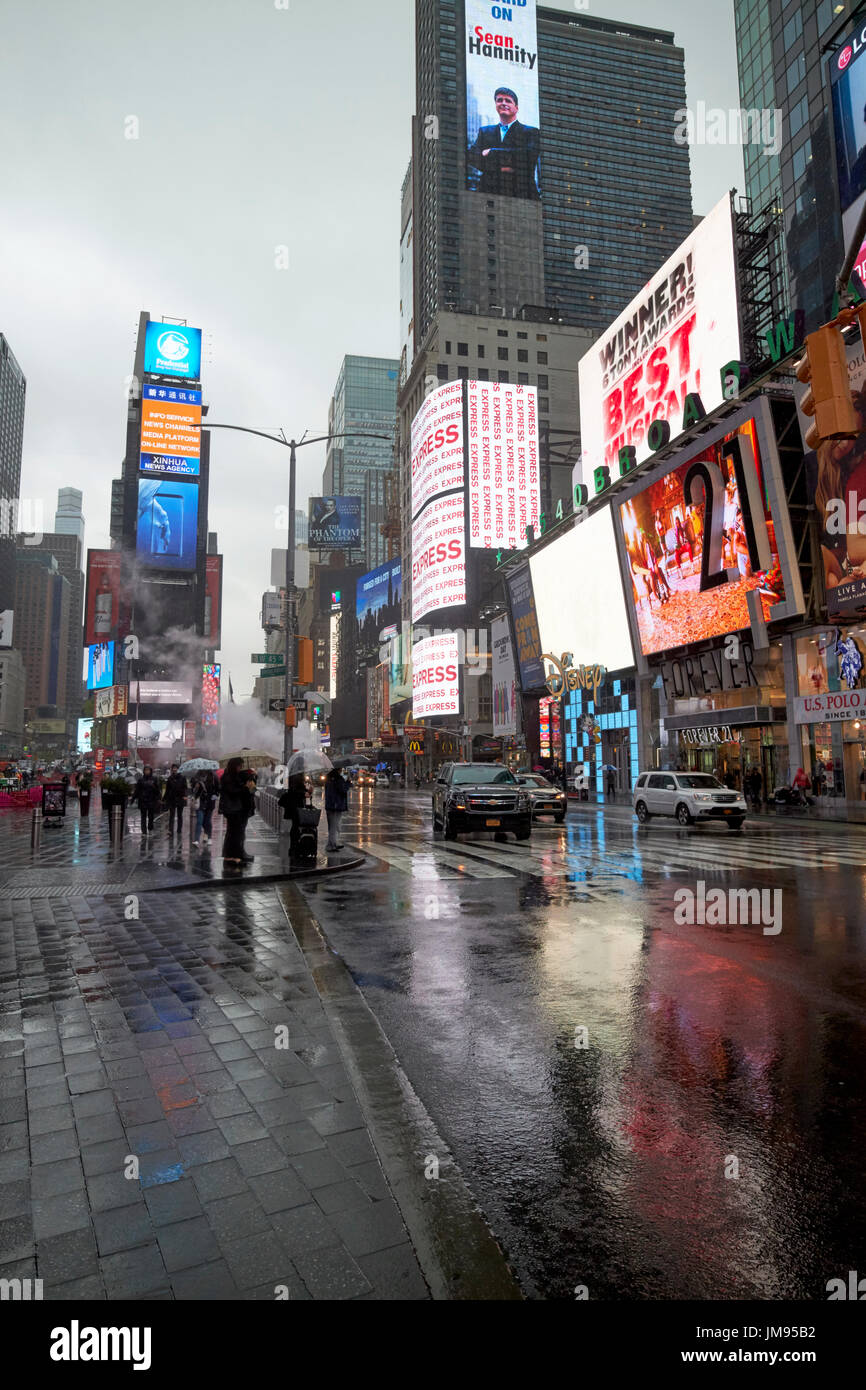 reflections of screens in times square on streets in the rain New York City USA - Stock Image