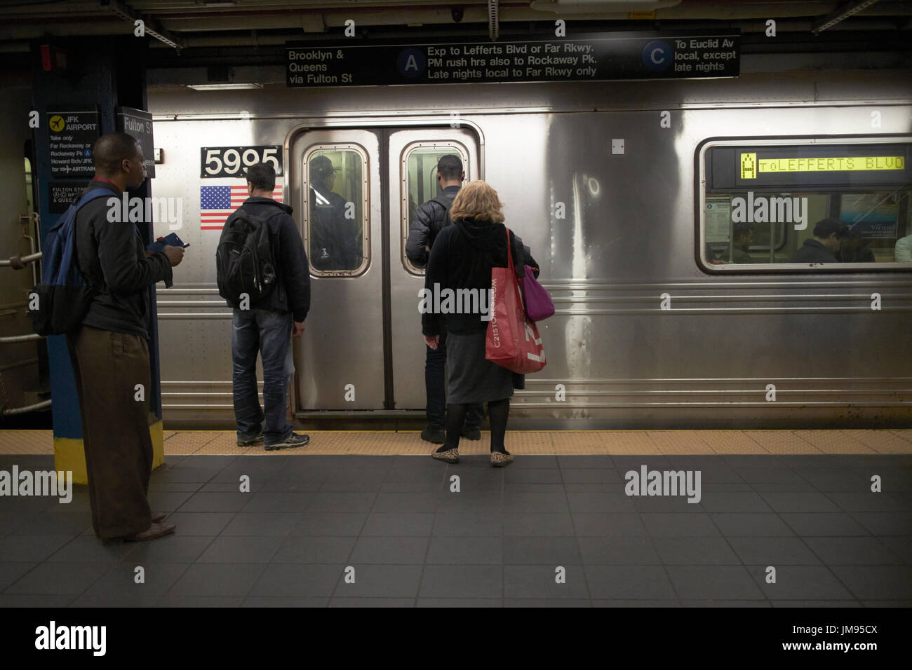 people waiting to board arriving train new york subway New York City USA - Stock Image