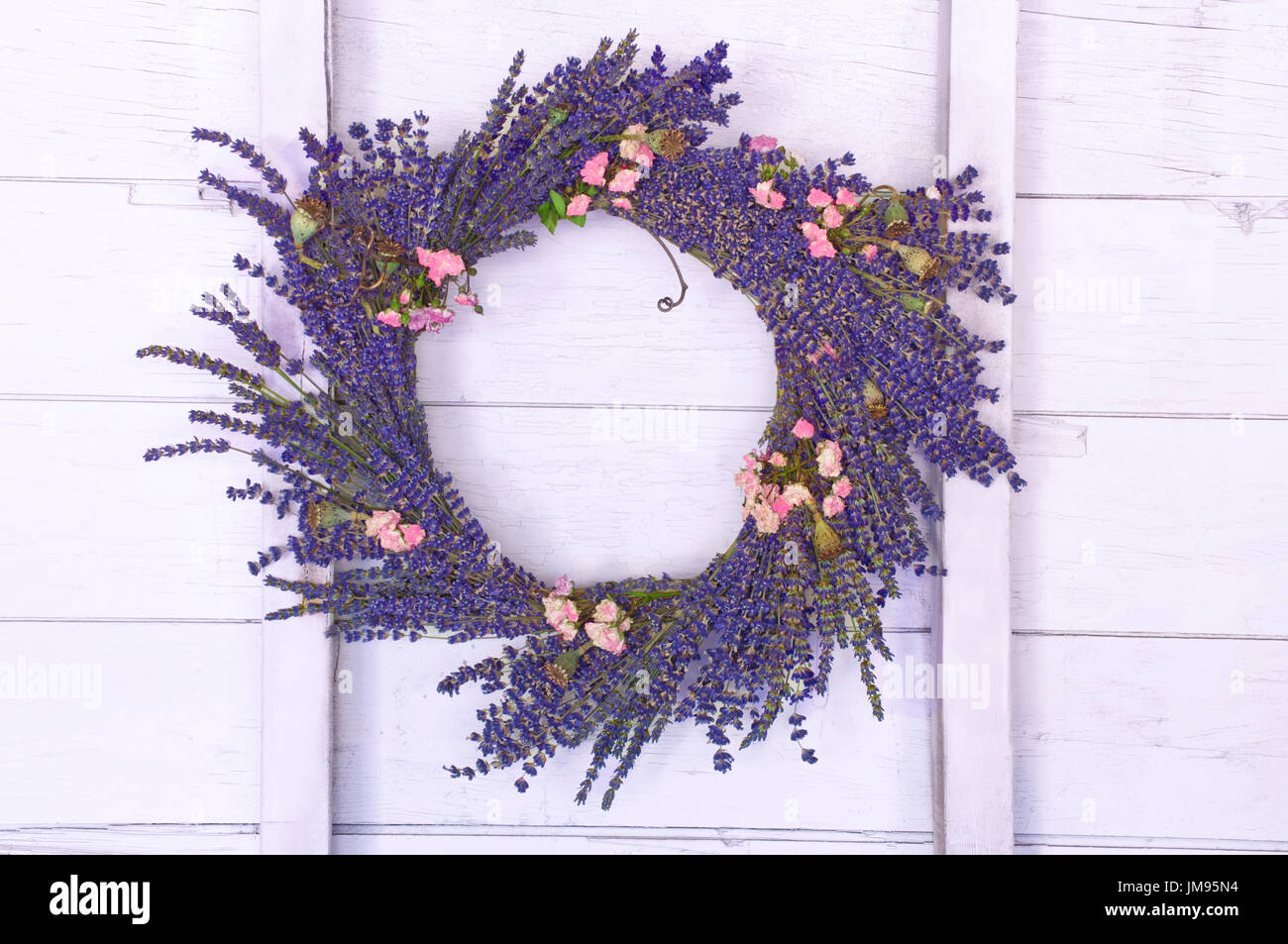 Lavender wreath hanging on wood wall in barn - Stock Image