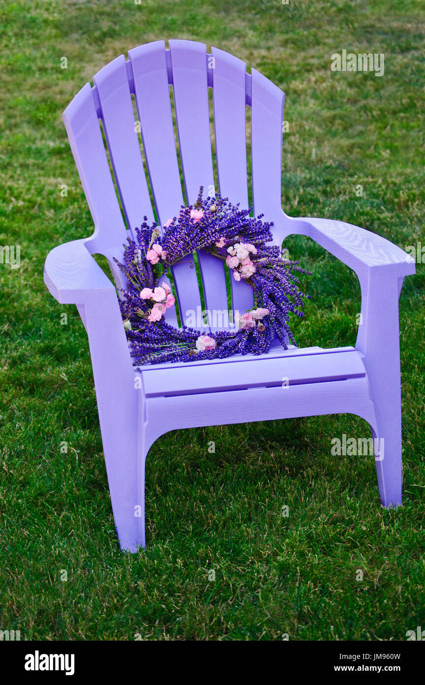 Purple lawn chair with lavender and fairy rose wreath - Stock Image