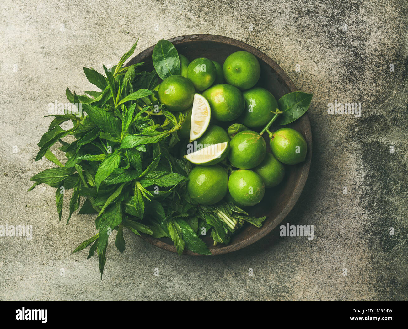 Flatlay of fresh limes and mint in wooden plate - Stock Image