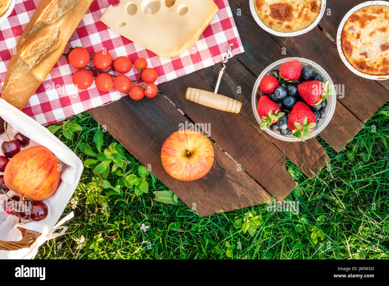 Overhead photo of picnic with apples, fresh fruit in plastic container, piece of Dutch cheese, quiches, baguette, and a corkscrew, on a rustic wooden  - Stock Image