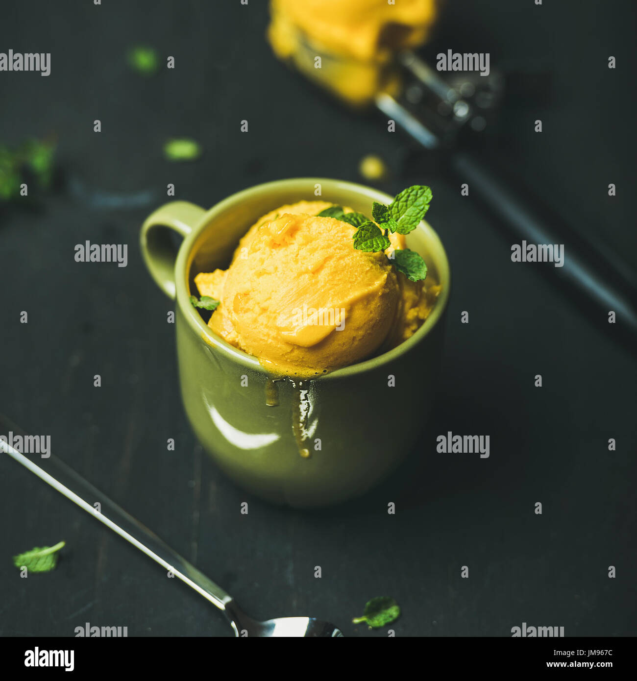 Mango sorbet ice cream scoops with fresh mint leaves - Stock Image