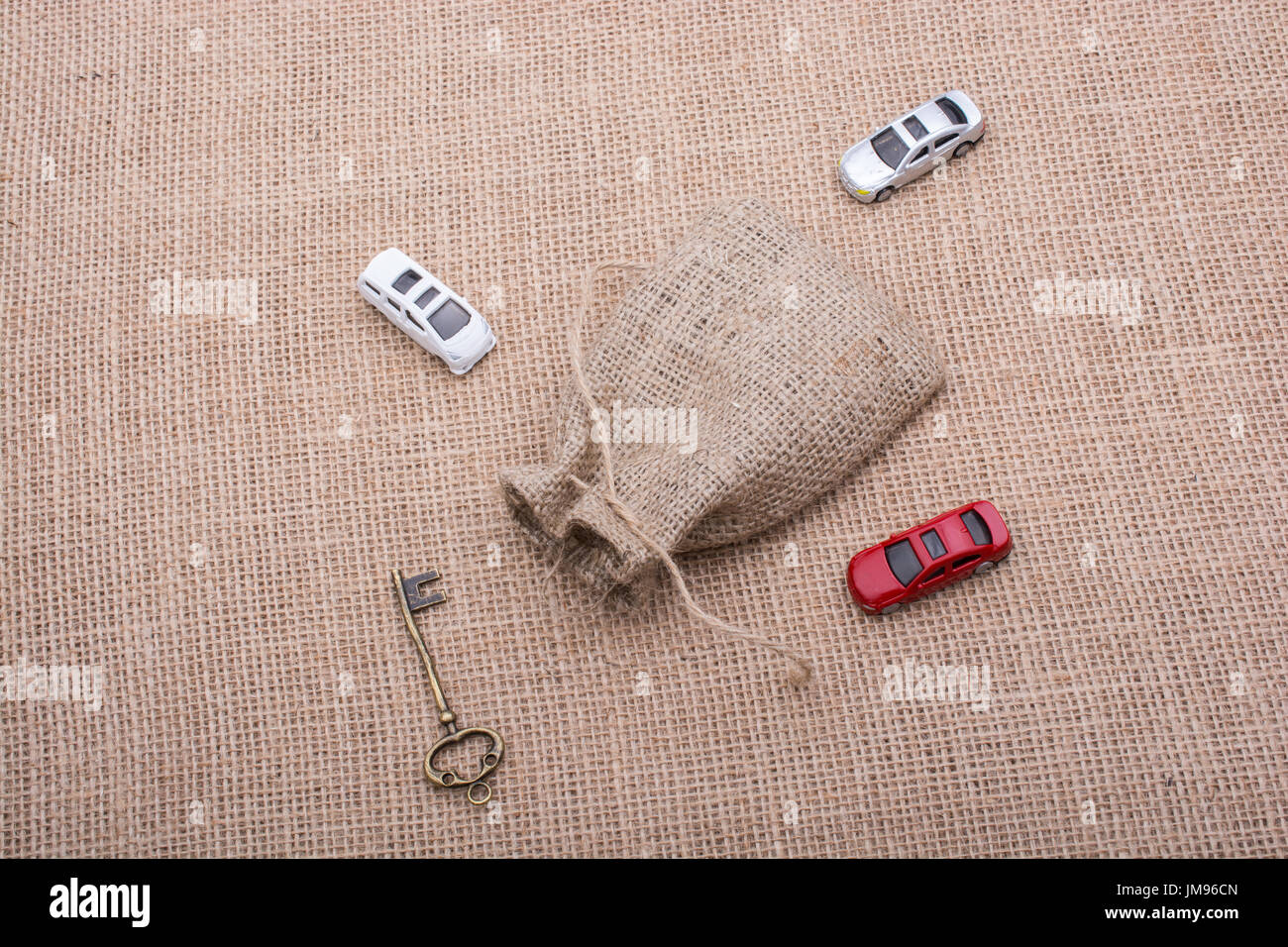 Key and toy cars around a sack on a linen canvas - Stock Image