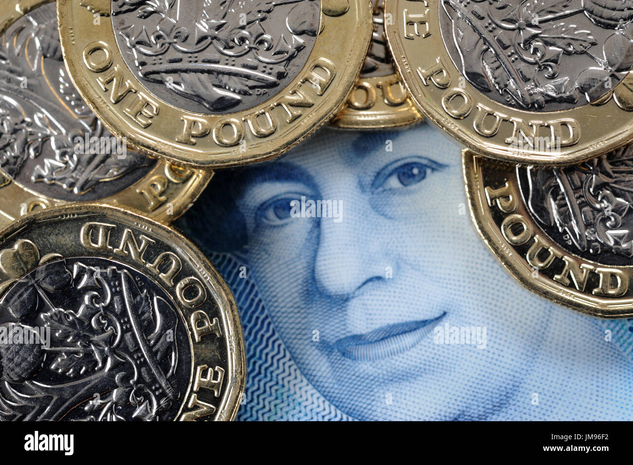 NEW ONE POUND COINS WITH QUEENS HEAD ON NEW FIVE POUND NOTE RE FINANCE BREXIT SAVERS SAVINGS HOUSEHOLD BUDGETS INFLATION Stock Photo