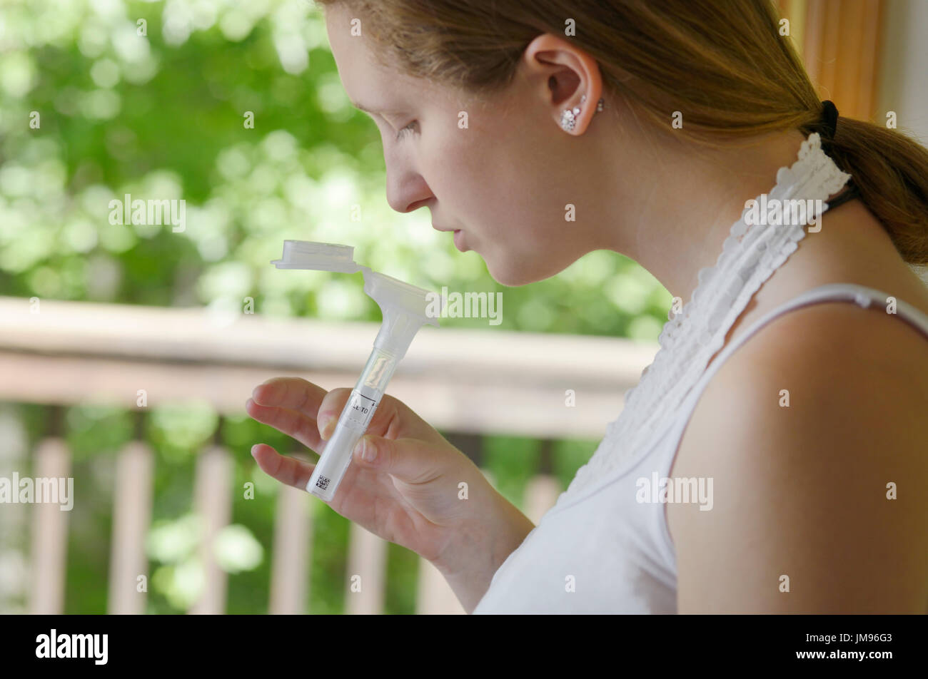 Girl collecting saliva for a mail-in DNA gene testing kit for ancestry and health genes - Stock Image