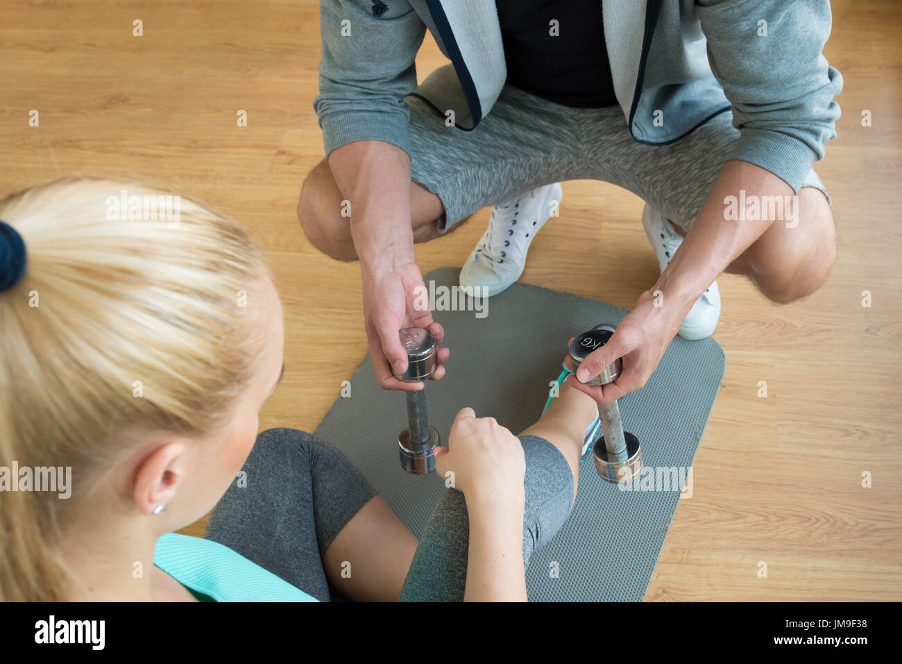 Personal trainer handing dumbbells to young woman during workout session - Stock Image
