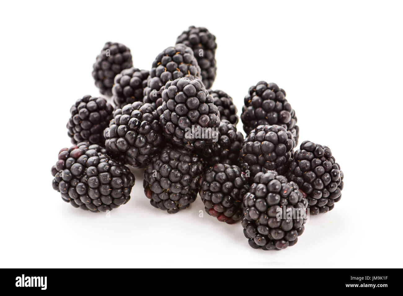 closeup of a pile of appetizing ripe blackberries on a white background - Stock Image