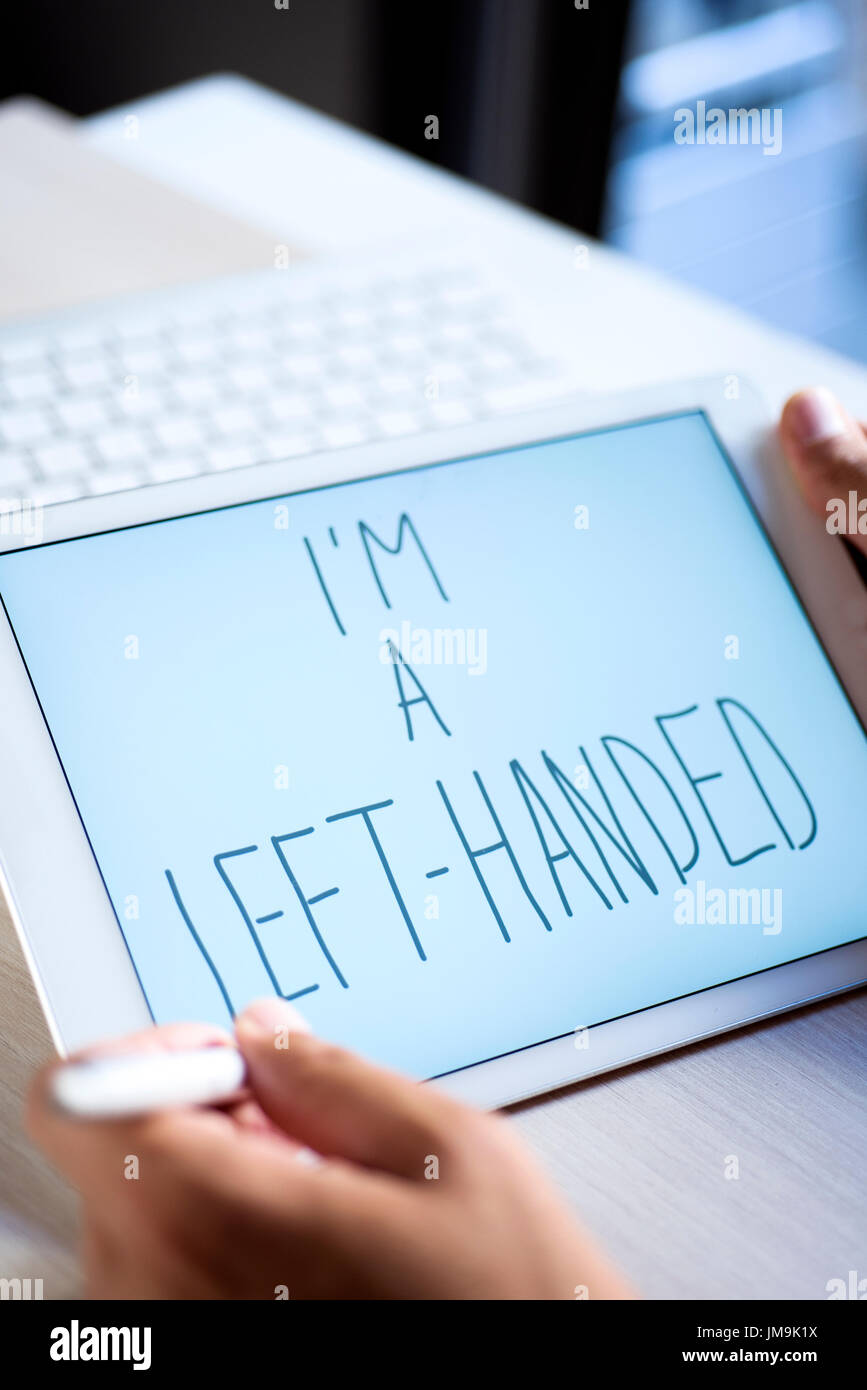 closeup of a young left-handed man handwriting the text I am a left-handed in digital tablet with an active pen - Stock Image