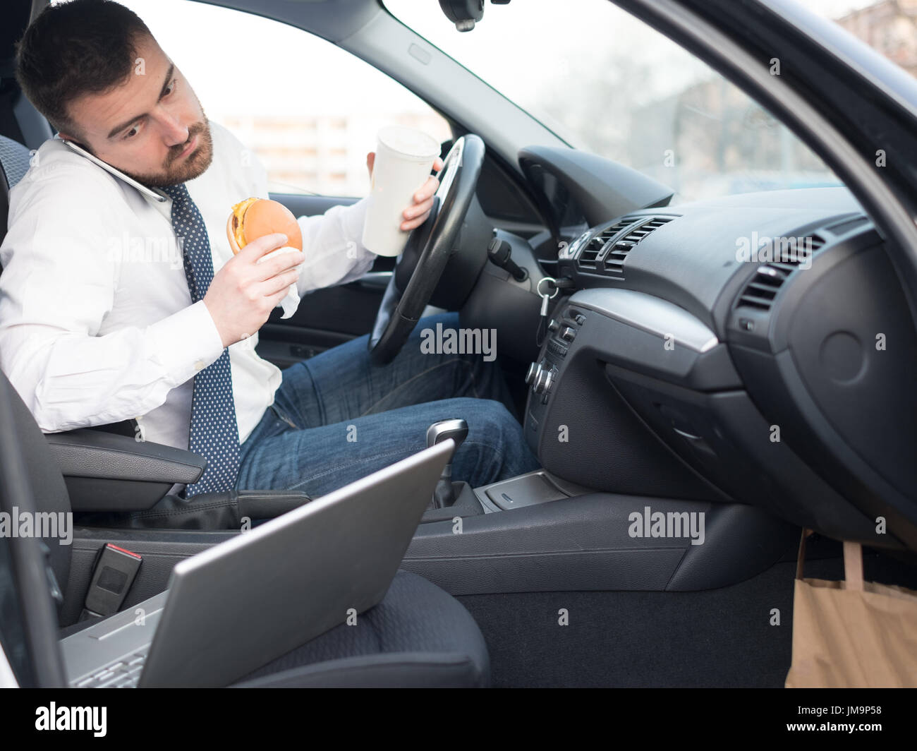 Man eating an hamburger and working seated in his car - Stock Image
