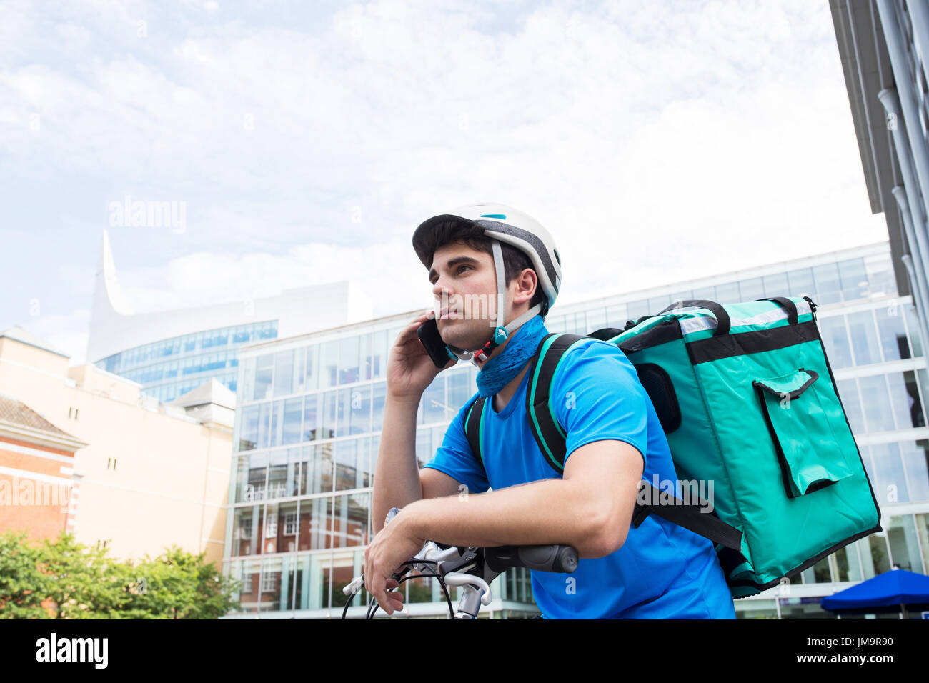 Courier On Bicycle Delivering Food In City Using Mobile Phone Stock Photo
