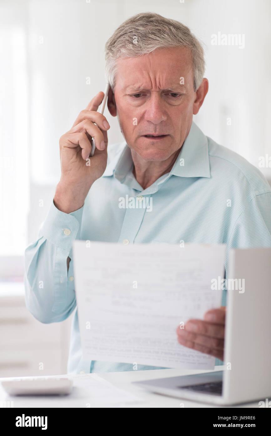 Unhappy Senior Man On Phone Querying Bill - Stock Image