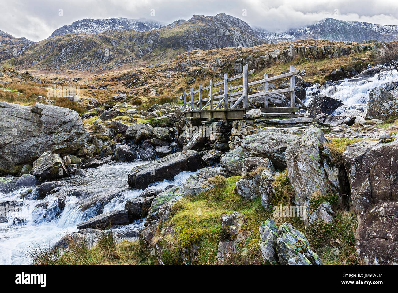 Bridge across waterfall near Llyn Ogwen on the path to Llyn Idwal and the Devil's Kitchen in the Glyderau mountain range Snowdonia North Wales UK - Stock Image