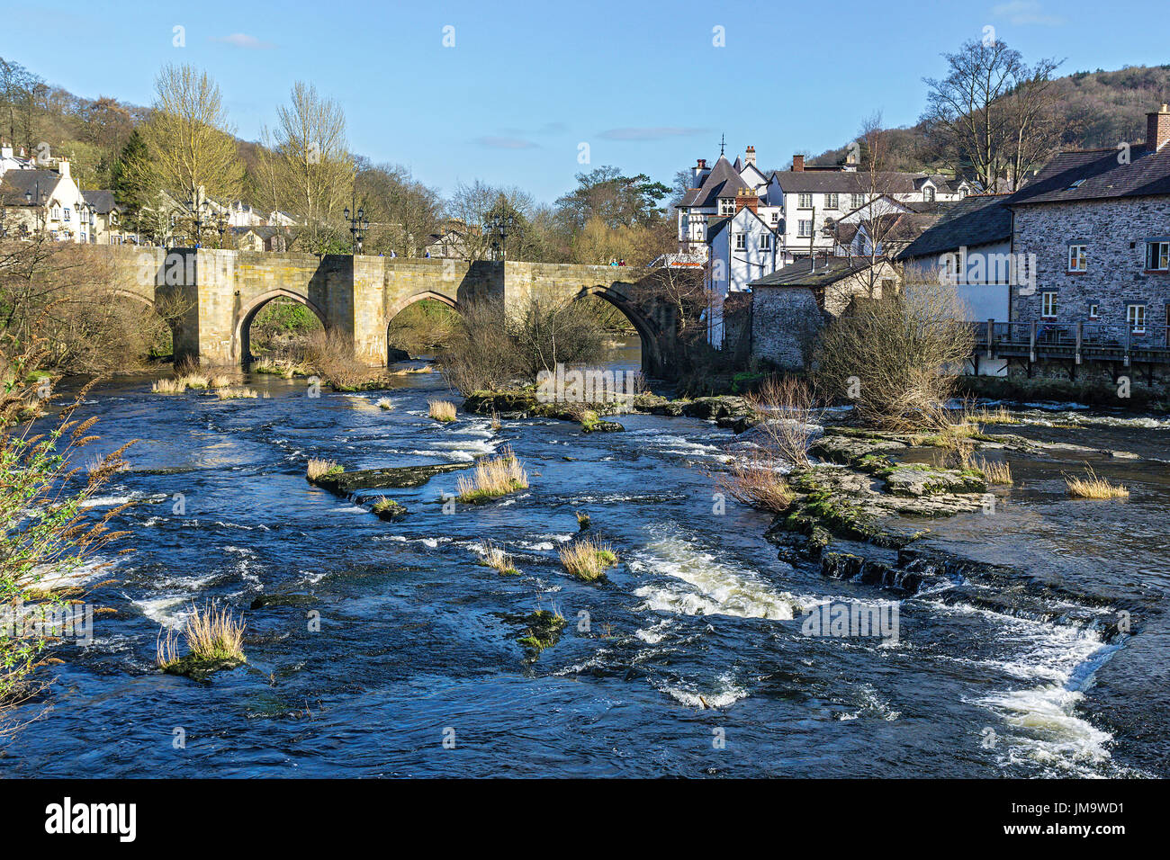 River Dee flowing through the centre of Llangollen showing the Dee Bridge a scheduled ancient monument Denbighshire Wales UK March 3081 - Stock Image