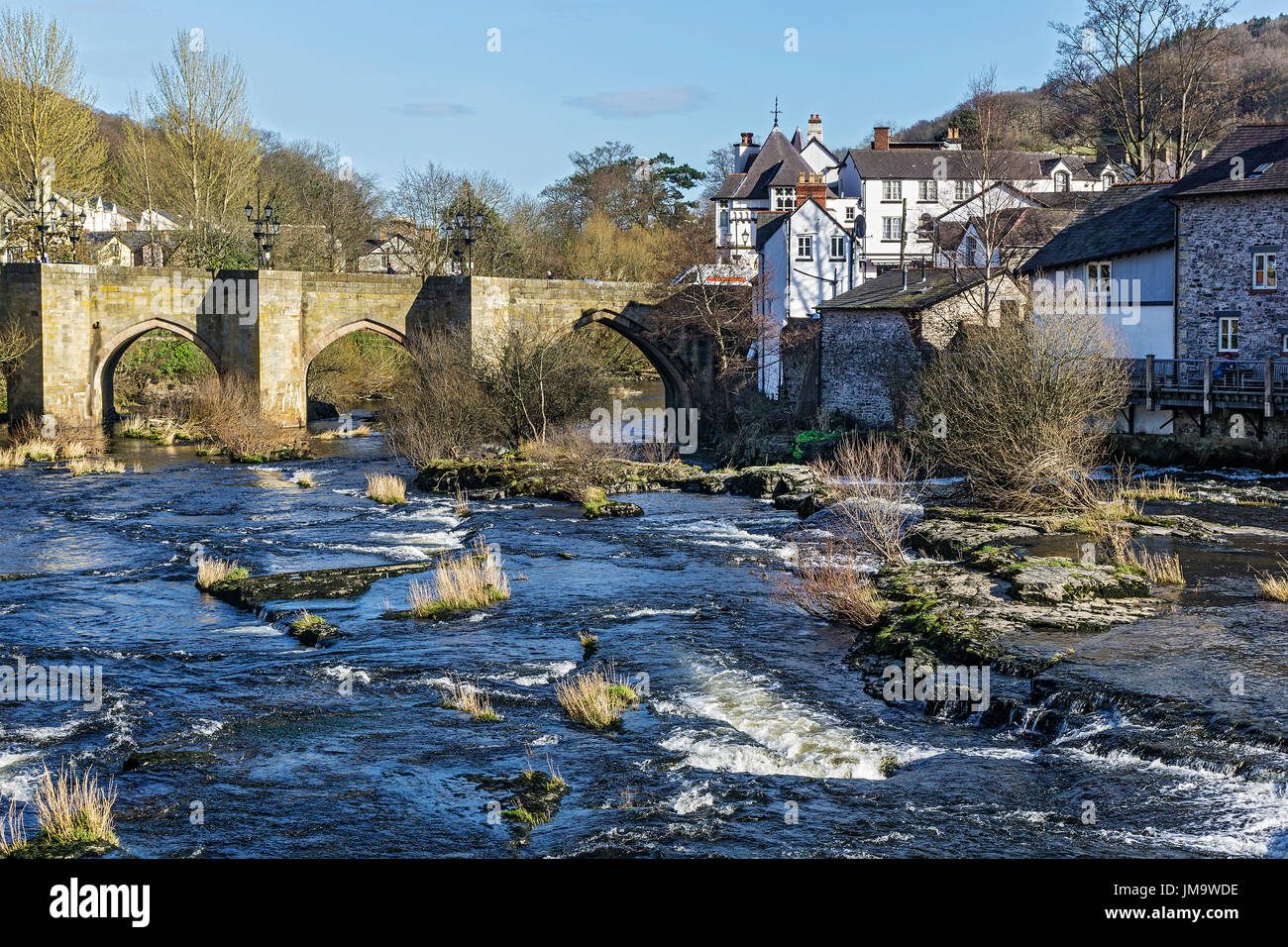 River Dee flowing through the centre of Llangollen showing the Dee Bridge a scheduled ancient monument Denbighshire Wales UK March 3095 - Stock Image
