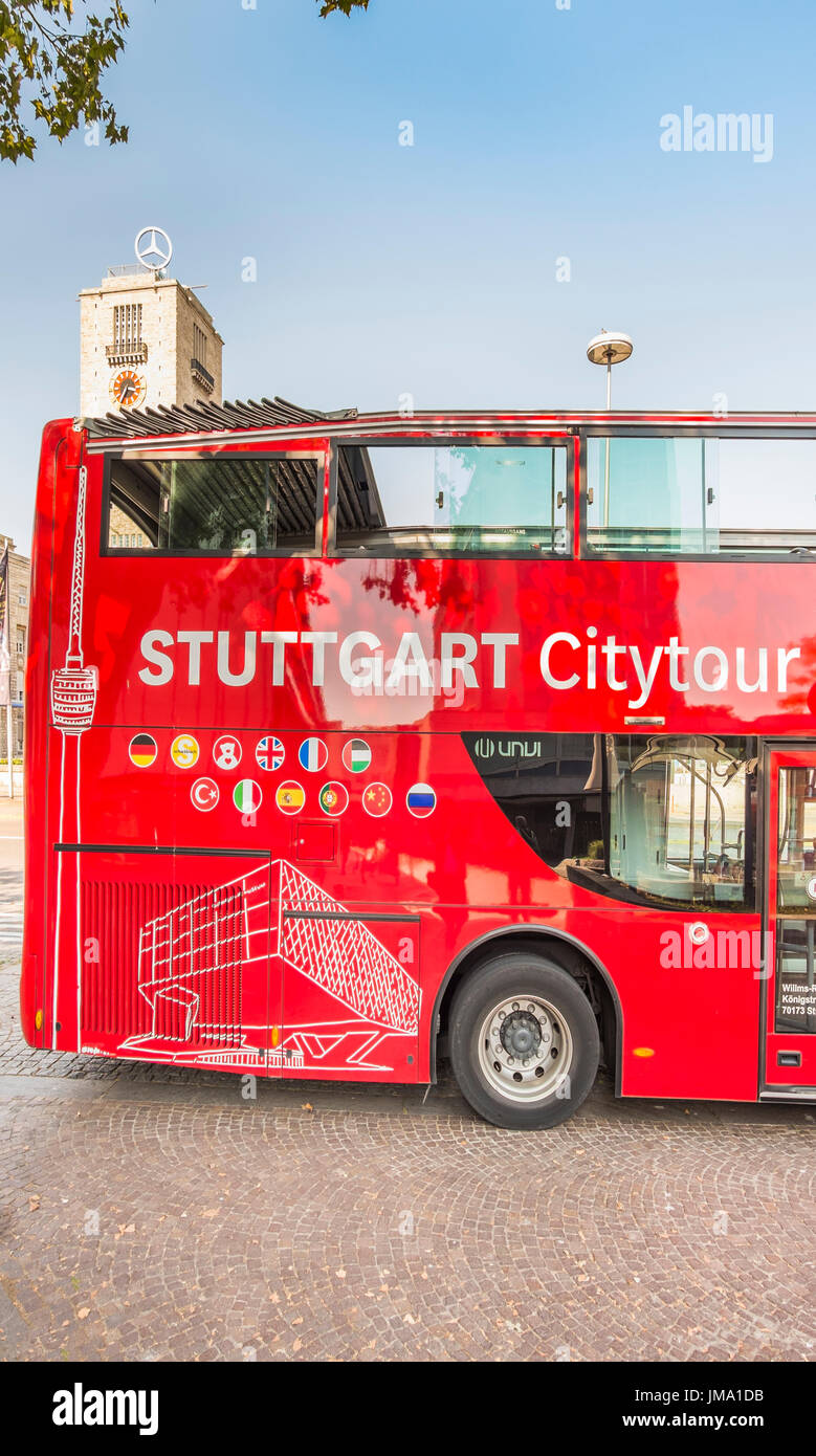 red stuttgart city tours bus, tower of central station with mercedes star in background, stuttgart, baden-wuerttemberg, germany - Stock Image