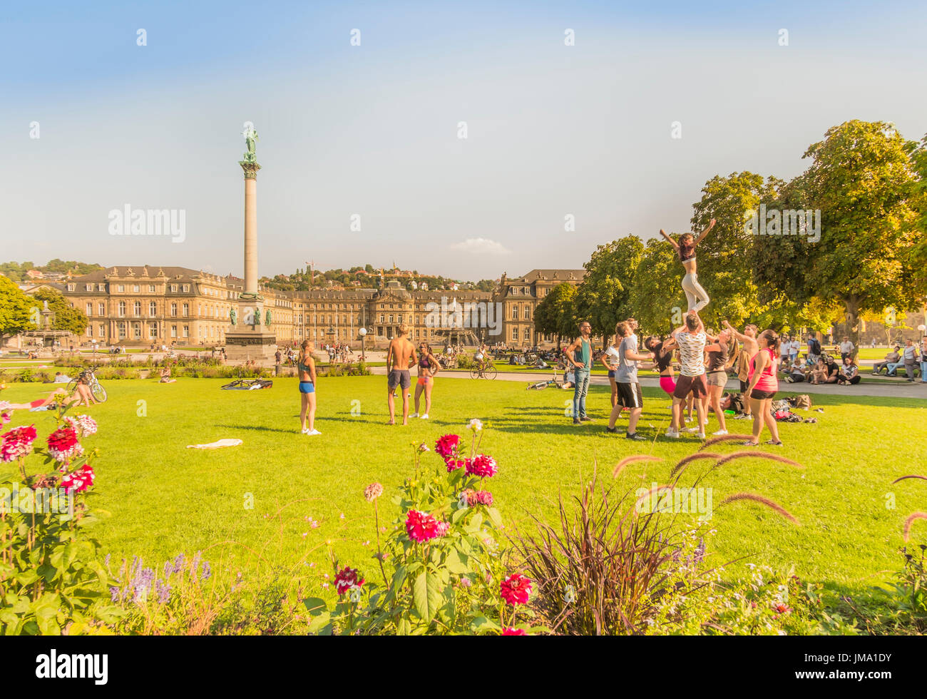 group of young people doing gymnastics in the garden in front of the new castle (neues schloss), stuttgart, baden-wuerttemberg, germany - Stock Image
