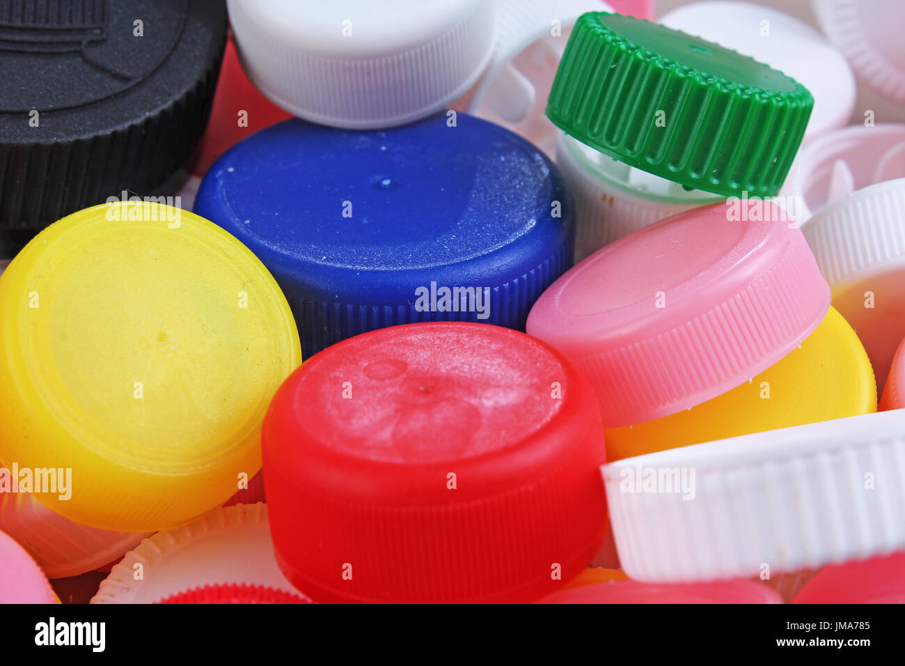 Collect plastic bottle caps.  Close-up shot of stack of recyclable plastic bottle caps on white background. Bottle cap texture pattern as background. - Stock Image