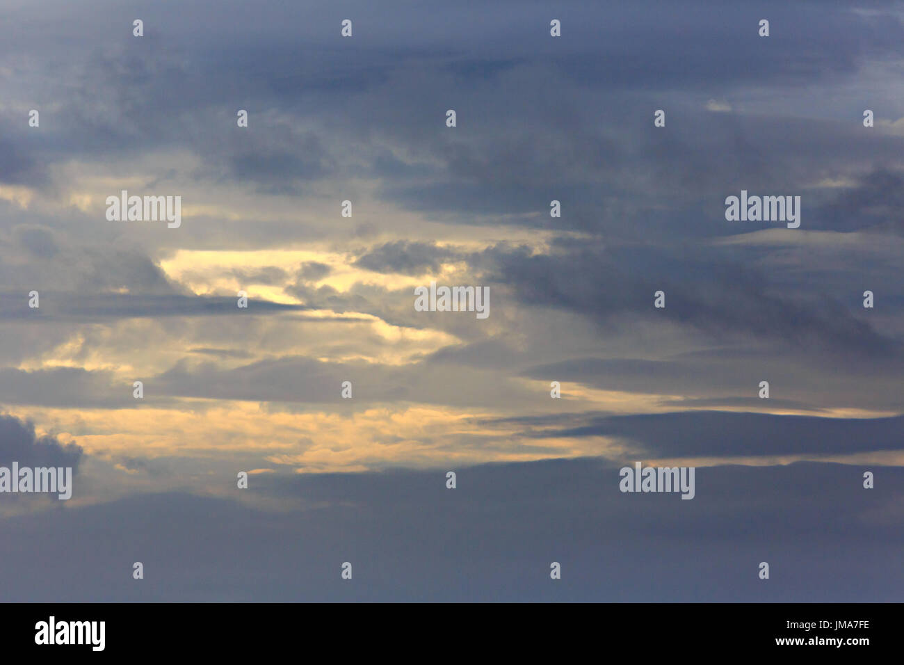 dark clouds with spots of late afternoon sunlight, just before sundown - Stock Image