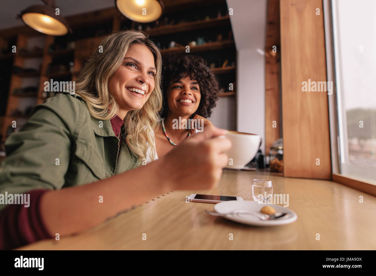 Two young woman sitting at cafe and having coffee. Female friends drinking coffee at restaurant. - Stock Image