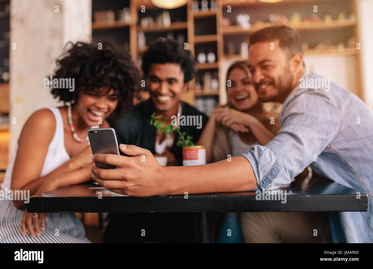 Young men and women sitting at cafe table and taking a self portrait with mobile phone. Multiracial group of friends Stock Photo