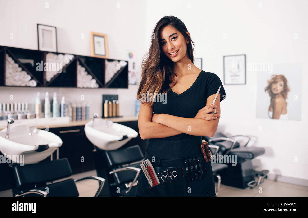 Female hairdresser in salon holding scissors in hand. Smiling young hairdresser standing in salon. - Stock Image
