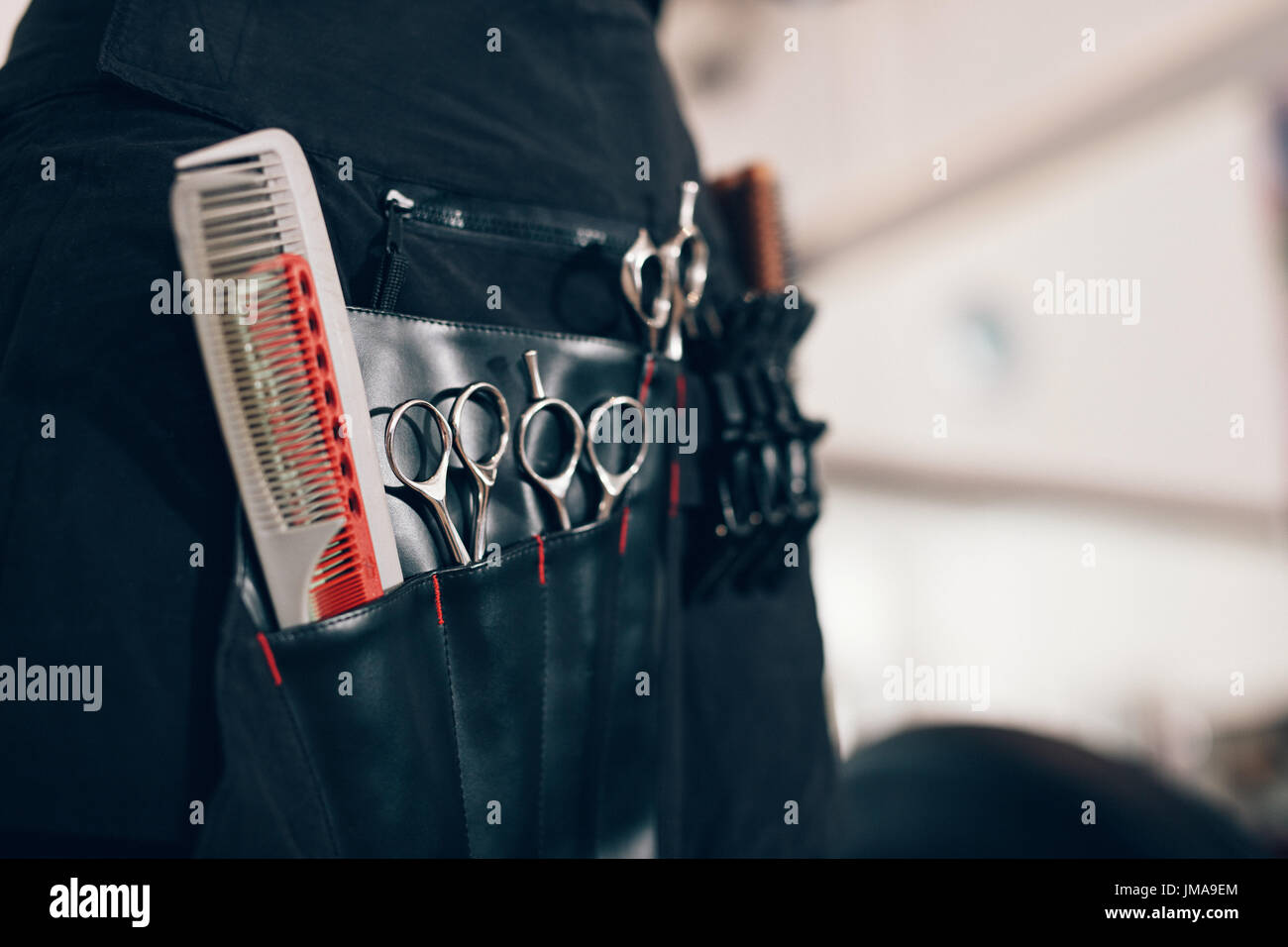 Closeup of scissors and combs in a salon holster pouch. Hairdressing tools inside a hairdresser waist pouch. - Stock Image