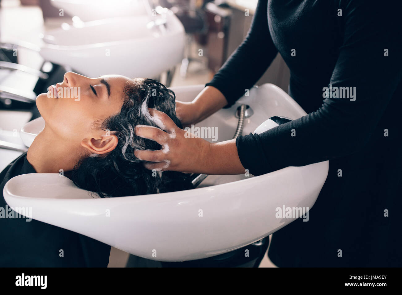 Woman applying shampoo and massaging hair of a customer. Woman having her hair washed in a hairdressing salon. - Stock Image