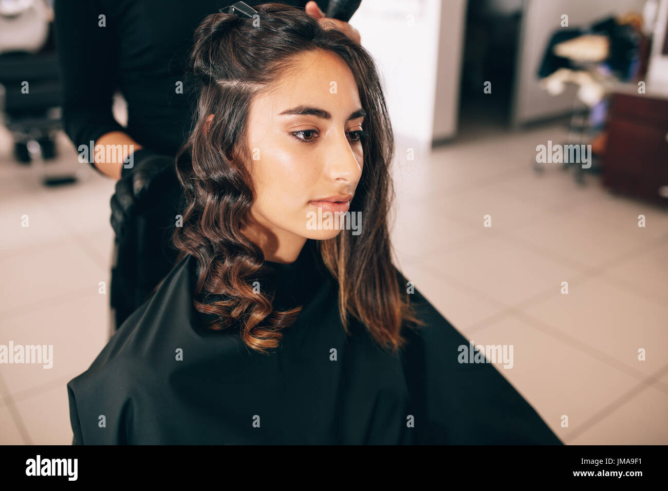 Close up of young woman at the salon getting her hair styled. Hair stylist turning straight hair into curly. - Stock Image