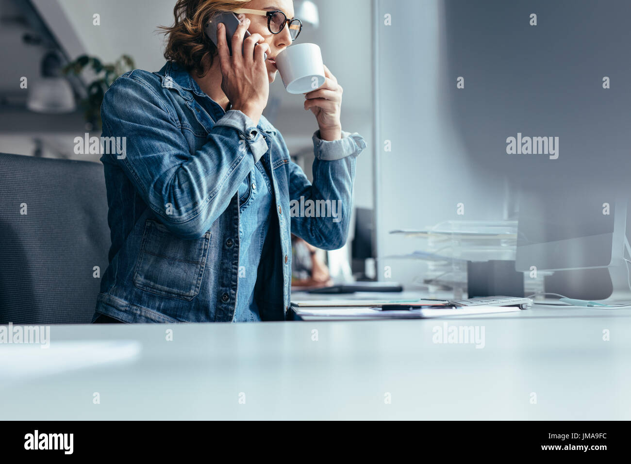 Female at work drinking coffee and talking on mobile phone. Young businesswoman at work making phone call and having coffee. - Stock Image
