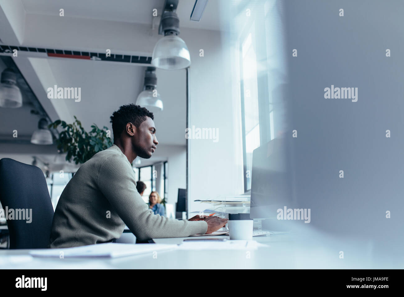 Side view of young african man working in office. Male executive sitting at his desk and working on desktop computer. - Stock Photo