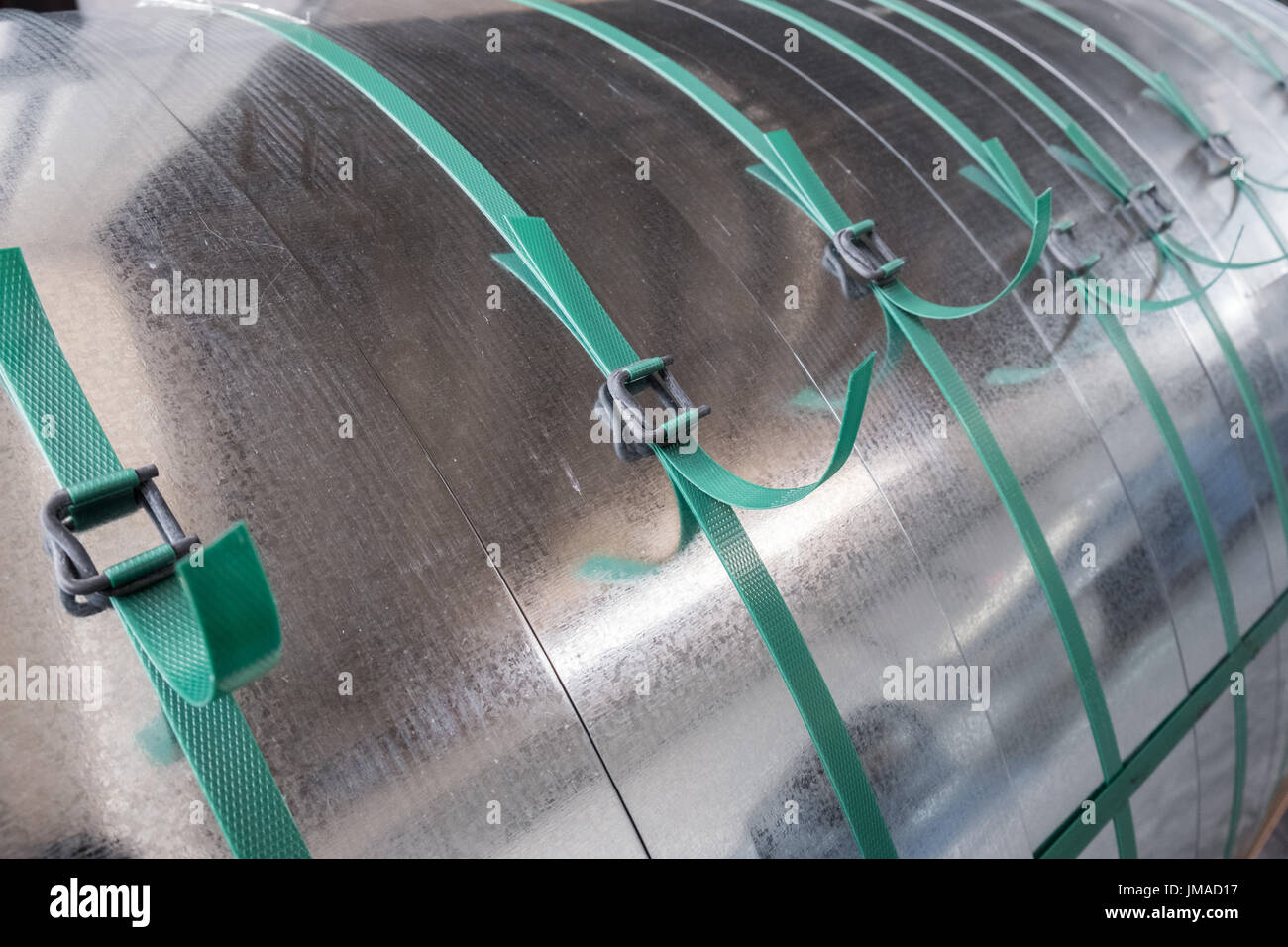 Galvanized steel coils strapped tied by plastic strips - Stock Image